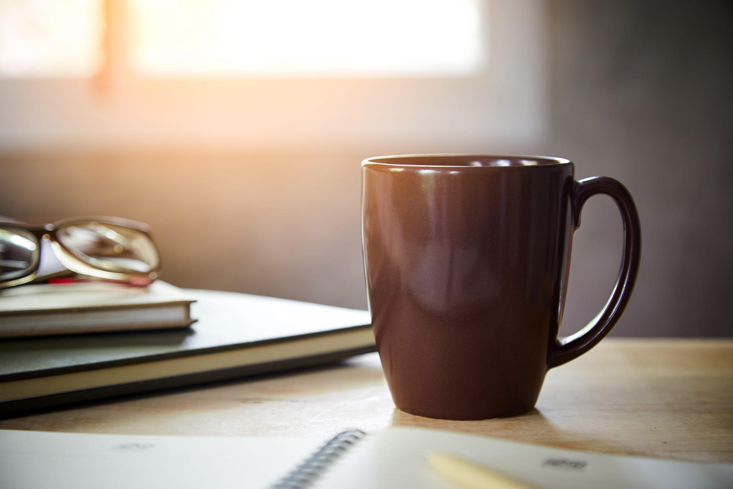 Morning coffee on the desk with sunlight from window,  Coffee mug on the table with the blurred of notebook and glasses