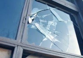 broken window reflecting blue sky