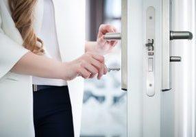 Locking or unlocking modern door with key in hand