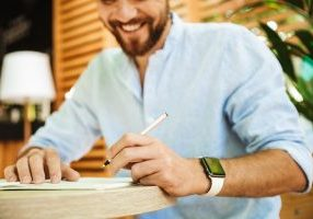 Cropped image of young bearded man outdoors writing notes.