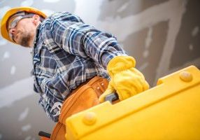 Professional Remodeling Contractor with Yellow Case with Power Tools Inside. Caucasian Worker in Yellow Hard Hat in His 30s.