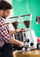 Satisfied barista steaming milk at coffee machine