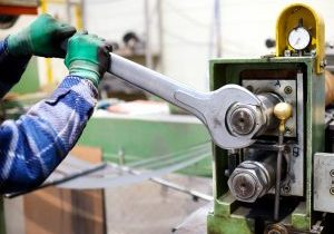 Worker adjusting machinery with large metal wrench