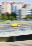 Yellow delivery van in rush, motion blur effect, panoramic city view