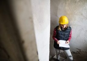 Female worker on the building site. Beautiful young woman holding blueprints. House construction.